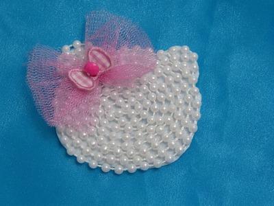 Carita de Hello kitty elaborada en fieltro y perlas para decorar accesorios del cabello