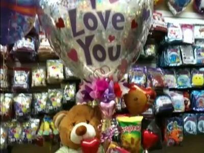 Un gran oso de peluche en este arreglo con globos para san V
