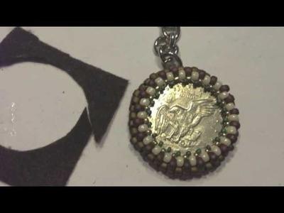 Llavero con  moneda bordada en piedras .